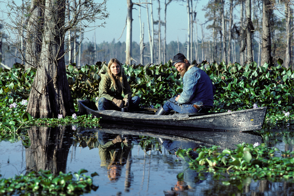Gwen and Calvin relax in pirogue in water hyacinth covered Sawyer's Cove
