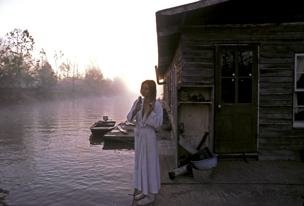 Gwen Carpenter on deck of her houseboat at sunrise