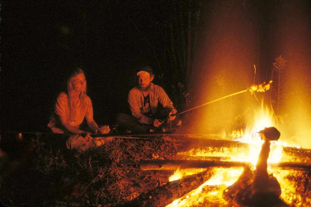 Calvin and Gwen roasting sausage and vegetables over campfire behind the house boat they lived on in the Atchafalaya Basin.