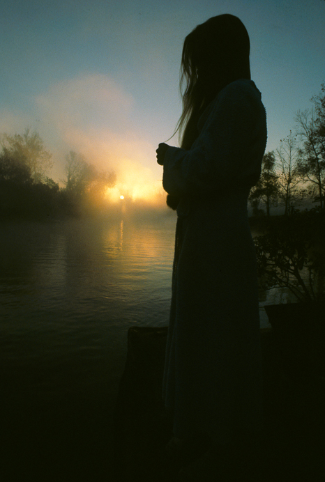 Gwen Carpenter at sunrise on deck of house barge Atchafalaya Basin, Louisiana, USA