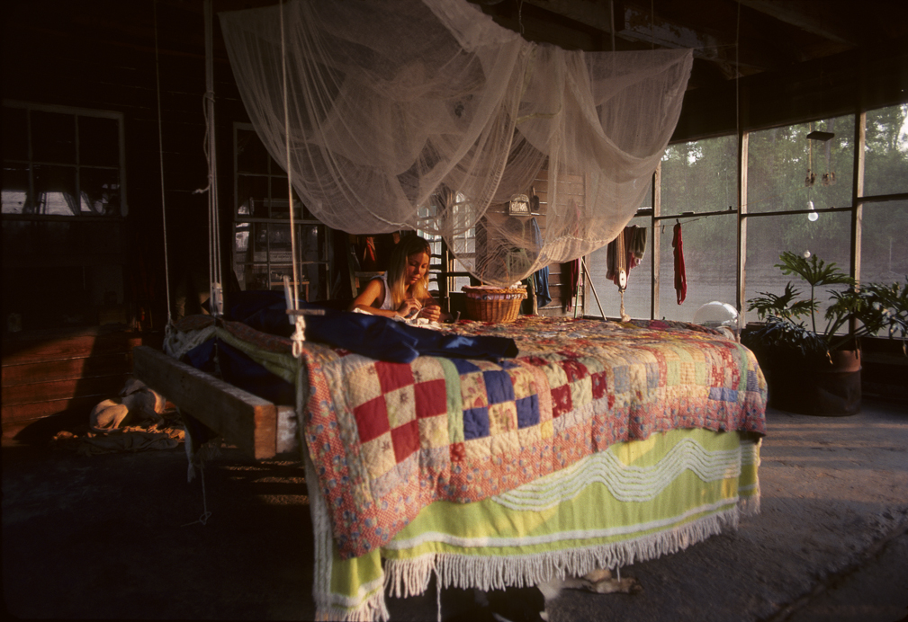 Gwen Carpenter does quiliting on her porch of house boat